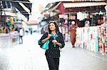 Mature female tourist strolling in market at Sharjah, United Arab Emirates