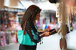 Mature female tourist looking beaded purse on market stall, Sharjah, United Arab Emirates