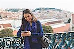 Woman texting on smartphone, Lisbon, Portugal