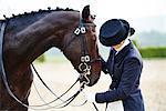 Female rider petting dressage horse in equestrian arena