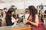 Hairdresser getting receipt for female customer in hair salon