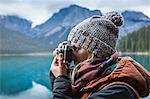Woman taking photograph of view, Emerald Lake, Yoho National Park, Field, British Columbia, Canada