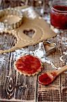 Jam being spread onto unbaked vegan shortbread biscuits