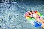 Girl in bikini lying on inflatable in outdoor swimming pool