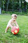 Barefoot female toddler picking up spotty ball in garden