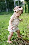 Barefoot female toddler in garden
