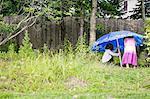 Boy and girl putting up beach umbrella in garden
