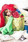 Boy sitting in basket amongst laundry