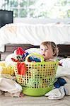 Female toddler sitting in basket amongst laundry