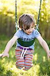 Boy lying on front swinging on garden swing