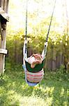 Boy upside down swinging on garden swing