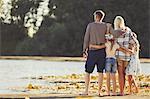 Family hugging at sunny lakeside