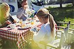 Girl using digital tablet at breakfast table outside sunny motor home