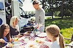 Family eating breakfast at table outside sunny motor home