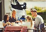 Family enjoying breakfast at table outside sunny motor home