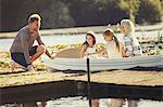 Family in canoe at sunny lake dock
