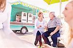 Smiling senior business owners using digital tablet outside food cart
