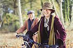 Smiling senior couple bike riding in sunny autumn woods