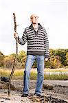 Mature man holding a stick