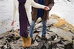 Mature couple climbing rocks