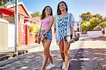 Two female friends, walking outdoors, carrying skateboards