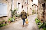 Rear view of woman walking in narrow rural street, Bruniquel, France