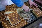 Baker cutting freshly-made focaccia