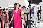 Stylist fastening fashion model's dress in photography studio
