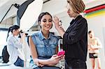 Make up artist applying eye shadow to model in photography studio