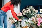 Female florist arranging roses in vase for shop display