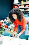 Female florist preparing labels for flower arranging workshop