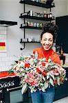 Portrait of mid adult female florist holding flower bouquet in florists workshop
