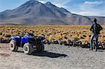 Man by quad bike looking at mountain, San Pedro de Atacama, Chile
