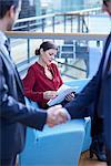 Businessmen shaking hands looking at businesswoman reading paperwork in office atrium