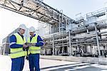 Workers using digital tablet in oil blending factory