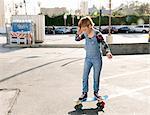 Girl wearing dungarees skateboarding