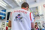 Hairdresser cutting hair in barbershop