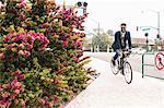 Young man cycling onto rail station platform