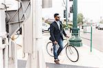 Young man pushing bicycle on rail station platform