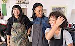Female barbers laughing in team meeting in barber shop