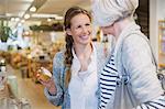 Smiling daughter showing mother jar in shop