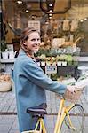 Portrait smiling woman walking bicycle at urban storefront