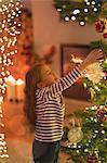 Girl hanging ornament on Christmas tree