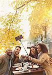 Smiling friends taking selfie with selfie stick at autumn sidewalk cafe
