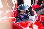 Formula one race car driver in helmet gesturing, celebrating victory