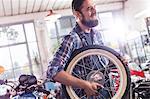 Smiling motorcycle mechanic carrying wheel in shop
