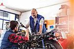 Motorcycle mechanics fixing motorcycle in workshop