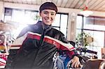 Portrait confident female motorcycle mechanic in workshop