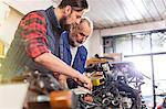 Motorcycle mechanics repairing motorcycle in workshop