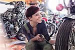 Enthusiastic female motorcycle mechanic repairing motorcycle in workshop